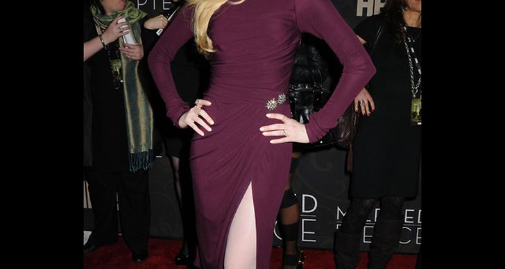 ... är stilig i en lila klänning med slits.