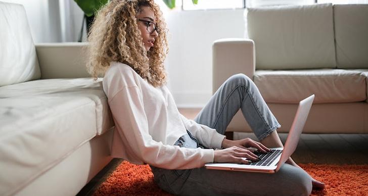 En tjej som sitter med sin dator