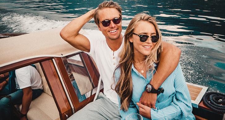 Jon och Janni Olsson Delér sitter på en båt och Jon håller sin arm om Janni.