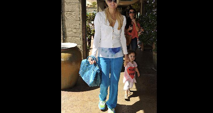Paris Hilton i blå byxor och med lilla kusinen i handen.
