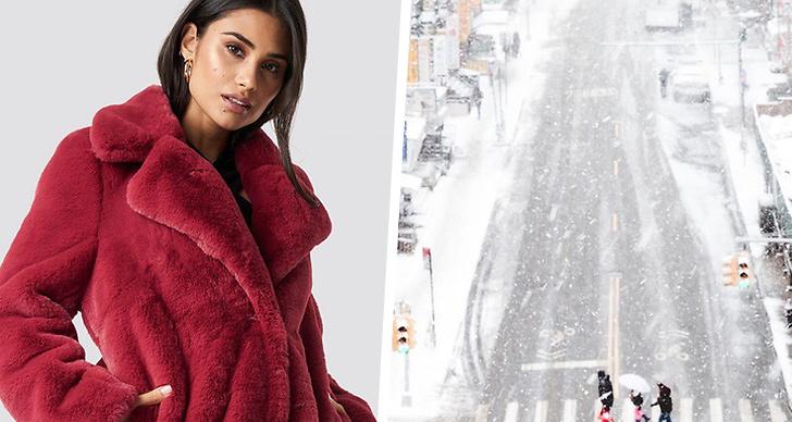 Till vänster en tjej med en röd fuskpäls jacka på sig, till höger en stad som är täckt av snö.