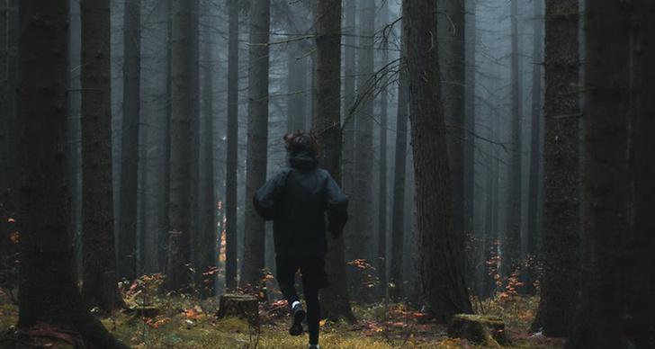 En kille som springer i skogen