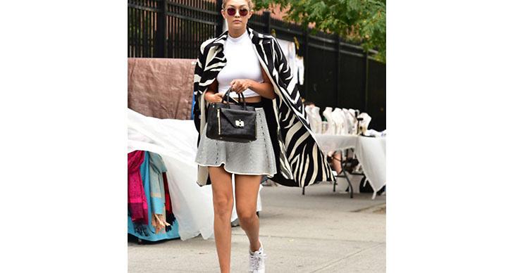 Gigi Hadid matchar en printad jacka med en minimalistisk kjol och ett par sneakers. Vi skulle säga att detta räknas som en perfekt vardagsoutfit.